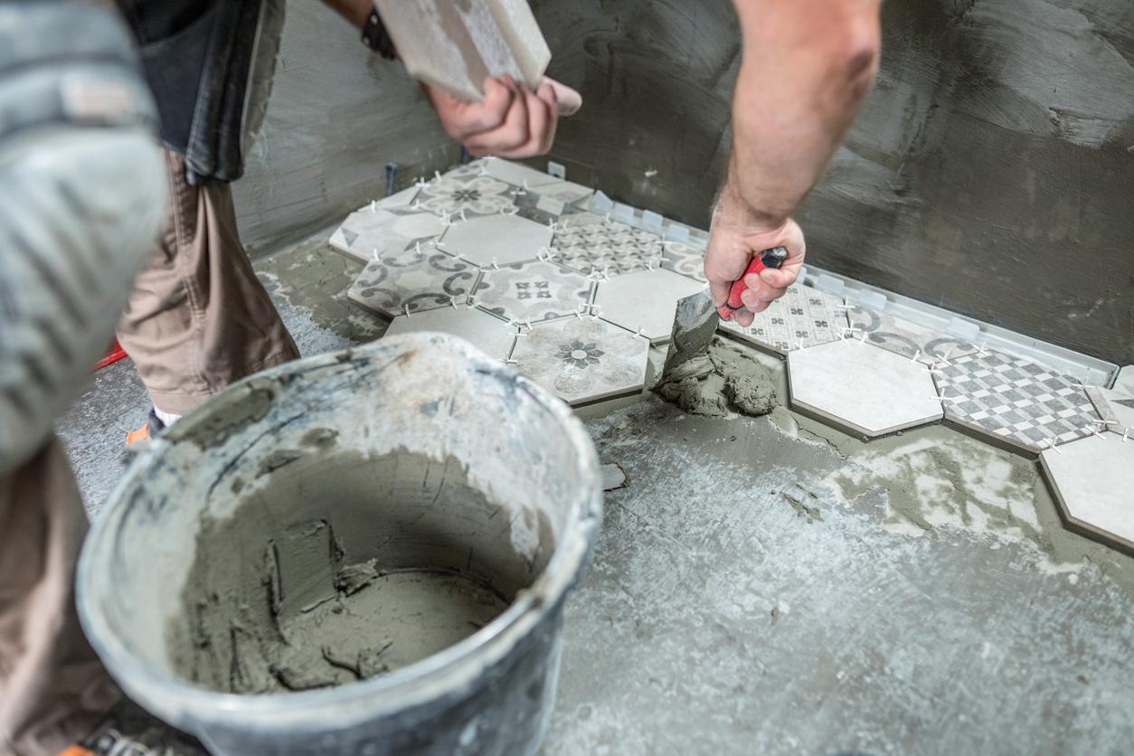 Professional tiler installing tiles on the bathroom floor